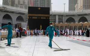 Petugas memakai masker wajah pelindung saat mereka membersihkan lantai di Masjidil Haram di kota suci Mekah, Arab Saudi, 3 Maret 2020. REUTERS